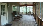 This picture of cabin 3 is taken on the porch from behind the swing. Also pictured are the two rocking chairs that is common to cabins 1-4. The porch is L shaped and runs the full length of both sides of the cabin. The porch has a wooden picnic table, chairs and a swing for your use. The porch has two access doors, one from the kitchen and the other is on the back side (other part of L shaped porch) between the fireplace and bedroom walls. The kitchen has a refrigerator, stove, range top, sink and dishwasher.