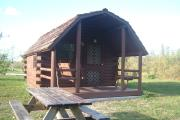 Photo: OLETA RIVER SP. Cabin #14 with swing on the porch and a picnic table outside.
