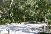 Photo shows an empty gravel pad with trees and vegetation surrounding the site. Site is a short distance from the playground, pavilion, parking, and the bathhouse.