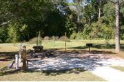 Photo shows an empty gravel pad with a couple small trees. There is only grass around the rest of the site. Site is a short distance from the playground, pavilion, parking, and the bathhouse.