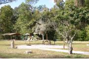Photo shows an empty gravel pad with playground and pavilion visible through trees a couple small trees. There is only grass around the rest of the site. Site is a short distance from parking and the bathhouse.
