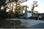 Photo shows a camper's tow-behind trailer, vehicle, and camping gear on the gravel pad. Photo shows some trees in the background and offers morning shade. This site is in front of wooden privacy fence.