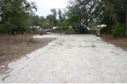 This photo shows an RV and vehicle on the fine gravel pad that is partially shaded. There is vegetation with some trees surrounding the site.