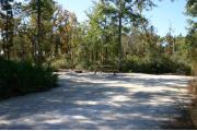 This photo shows an empty fine gravel pad that is partially shaded. There is vegetation surrounding the site.