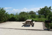 Photo: 008, View of gravel campsite with picnic table and grill, bushes in background.