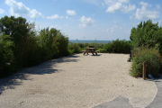Photo: 016, View of gravel campsite with picnic table and grill, Atlantic Ocean and bushes in background.