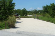 Photo: 018, View of gravel campsite with picnic table and grill, Atlantic Ocean and bushes in background.