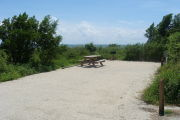 Photo: 019, View of gravel campsite with picnic table and grill, Atlantic Ocean and bushes in background.