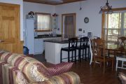 As an ADA cabin some alterations have been made to make the unit more user friendly. Otherwise the interior is pretty much the same as the other cabins. The main living area of the cabins offers two comfortable couches, and a wooden dining table with four wood chairs. An electric fireplace can be operated year round and can give off heat or be set so you can just watch the flames flicker. In the modern kitchen there is a dish washer, micro wave oven, stove, big refrigerator and an automatic coffee maker. Not seen are the two bedrooms and bathroom.