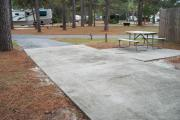 A view of RV site two at Topsail Hill Preserve State Park looking towards the front of the site.  A picnic table is on a concrete pad to the right of the site.