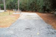 A view of RV site three at Topsail Hill Preserve State Park looking towards the back of the site.  A picnic table is on a concrete pad to the left of the site.