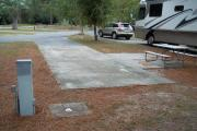 A view of RV site four at Topsail Hill Preserve State Park looking towards the front of the site.  A picnic table is on a concrete pad to the right of the site and utility hook up boxes are to the left.