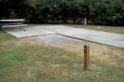 A view of RV site five at Topsail Hill Preserve State Park showing the site marker, a picnic table next to the site, and the utility hook up boxes.
