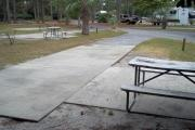 A view of RV site five at Topsail Hill Preserve State Park looking towards the front of the site.  A picnic table is on a concrete pad to the right of the site.  Other RV sites can be seen to the left of the site.
