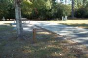 A view of RV site seven at Topsail Hill Preserve State Park showing the site marker, a picnic table next to the site to the left, and the utility hook up boxes to the right.