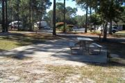 A view of RV site seven at Topsail Hill Preserve State Park looking towards the front of the site.  A picnic table is on a concrete pad to the right of the site.  The bathhouse and other RV sites are visible in the background.