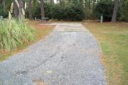 A view of RV site nine at Topsail Hill Preserve State Park looking towards the back of the site.  A picnic table is on a concrete pad to the left of the site and utility hook up boxes are to the right.