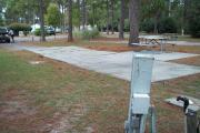 A view of RV site twelve at Topsail Hill Preserve State Park looking across the site.  A picnic table is on a concrete pad next to the site.  The utility hook up boxes are visible in the foreground.