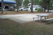 A view of RV site fourteen at Topsail Hill Preserve State Park looking across the site.  A picnic table is on a concrete pad next to the site.  The bathhouse is visible in the background.