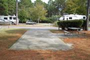 A view of RV site nineteen at Topsail Hill Preserve State Park looking towards the front of the site.  A picnic table is next to a concrete pad to the right of the site.  Other RV sites are visible in the background.