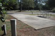 A view of RV site twenty at Topsail Hill Preserve State Park looking towards the front of the site.  A picnic table is next to a concrete pad to the right of the site and utility hook up boxes are to the left. Other RV sites are visible in the background.