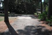 A view of RV site twenty-one at Topsail Hill Preserve State Park looking towards the back of the site.  A picnic table is on a concrete pad to the left of the site and utility hook up boxes are to the right of the site.