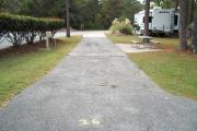 A view of RV site twenty-six at Topsail Hill Preserve State Park looking towards the back of the site showing that it is a pull through site open to the road at both ends.  A picnic table is on a concrete pad to the right of the site and the utility boxes are to the left.