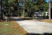A view of RV site twenty-seven at Topsail Hill Preserve State Park looking towards the back of the site.  A picnic table is on a concrete pad to the right of the site and utility hook ups are to the left of the site.