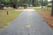 A view of RV site twenty-seven at Topsail Hill Preserve State Park looking towards the back of the site.  A picnic table is on a concrete pad to the left of the site and utility hook ups are to the right of the site.