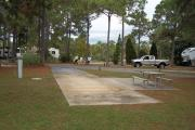 A view of RV site twenty-seven at Topsail Hill Preserve State Park looking towards the front of the site.  A picnic table is on a concrete pad to the right of the site and utility hook ups are to the left of the site.