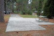 A view of RV site twenty-nine at Topsail Hill Preserve State Park looking towards the front of the site.  A picnic table is on a concrete pad to the right of the site.