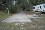 A view of RV site thirty-one at Topsail Hill Preserve State Park looking towards the front of the site.  A picnic table is on a concrete pad to the right of the site and the utility hook ups are to the left.