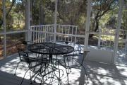 The screened in front porch of bungalow 1008 at Topsail Hill State Park.  A metal table with four chairs is sitting on the porch.