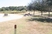 View of campsite #1 from site entry – This is a pull-through campsite, with an asphalt pad for camping units.  On the left of the asphalt pad is the electric hookup and water spigot, surrounded by a protective wooden enclosure.  On the right is a 12' x 20' concrete pad with a picnic table.  Near the concrete pad are a circular ground grill and a pedestal grill.