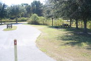 View of campsite #5 from site entry – This is a pull-through campsite, with an asphalt pad for camping units.  On the left of the asphalt pad is the electric hookup and water spigot, surrounded by a protective wooden enclosure.  On the right are a picnic table and a circular ground grill.