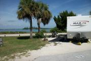 The back has a view of the inlet. The front is open to the street .There is a gravel drive in the center of the site. There are two sable palms next to a picnic table on the left. A white RV sits in the driveway.