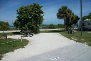 The back has a view of the inlet. The front is open to the street. There is a gravel drive in the center of the site. A picnic table sits in front of a sea grape on the left.  There is a fire ring on the far left.  Two sable palms are on the right.