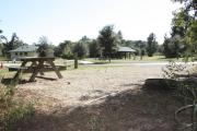 Photo: 010, SANTOS CAMPGROUND. View of campsite with water and electric hookups and picnic table with fire ring. Campground facilities can be seen nearby.