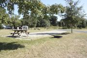 Photo: 021, SANTOS CAMPGROUND. View of campsite with water and electric hookups and picnic table with fire ring.
